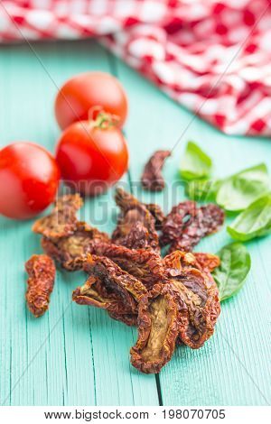 Dried sliced tomatoes and fresh tomatoes with basil leaves on colorful wooden table. Sundried tomatoes as superfood.
