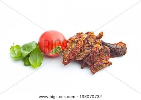 Dried sliced tomatoes and fresh tomatoes with basil leaves isolated on white background. Sundried tomatoes as superfood.