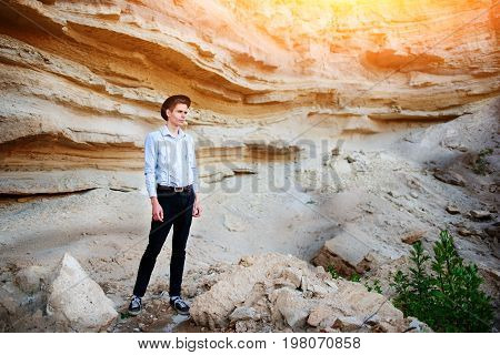 An Attractive Man Is Standing In The Middle Of A Sand Quarry And Looking Thoughtfully In The Distanc