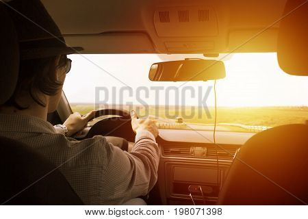 video recorder driving a car on highway. The hidden camera is hidden in the rear-view mirrorThe man in the hat drives the car. Sunset filter effect. Safety on the road. The road to success.