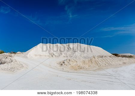 Chalk quarry. White sand hill, roads, blue sky. Limestone mining or desert concept