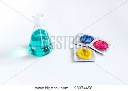 Visit the urologist. Flask and condoms on white background.