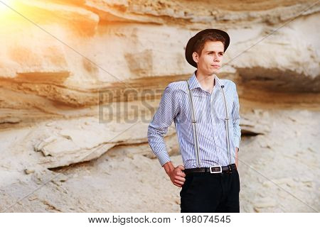 Stylish Attractive Man Stands In The Middle Of A Sand Quarry And Poses On The Camera