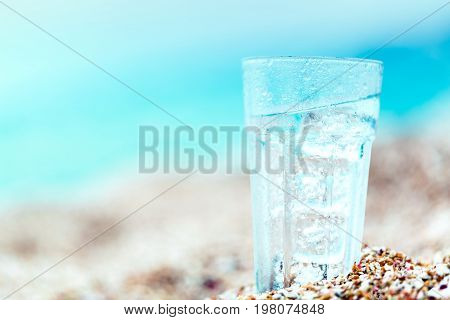 Glass water beach sand close up mineral water coconut water