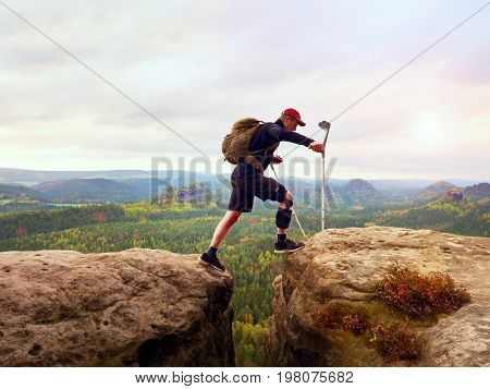 Tourist With Medicine Crutch Above Head Achieved Mountain Peak. Hiker With Broken Leg