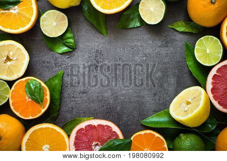 Fresh citrus fruit assortment. Whole and sliced citrus fruit on black slate table. Top view. Fruit food frame background. Healthy eating and diet.