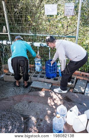 Cape Town South Africa - circa July 2017. As the devestating drought continues in the Western Cape Province of South Africa people in Cape Town are left with no choice other than to fill up water bottles and containers at the many mountain springs running