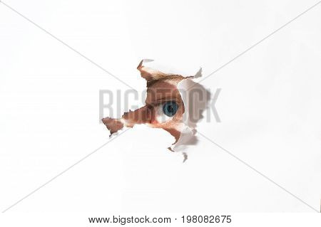 human Eye looking through a hole in a paper In the search for information answer decision free space