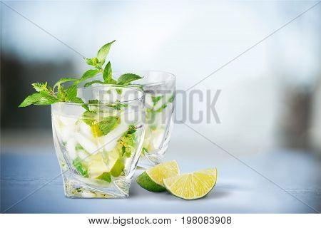 Delicious glasses lime cocktails bar color background