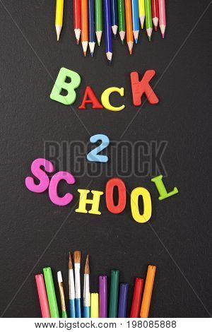 Back 2 school colorful letters and stationery on blackboard background with copyspace for your text. Concept for your design, banner, web, flyer.