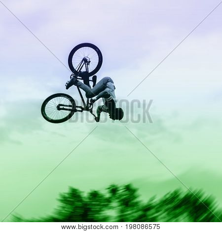 Silhouette of unidentified young man performs stunts on the background of vivid sky. Extrem Sport and risk