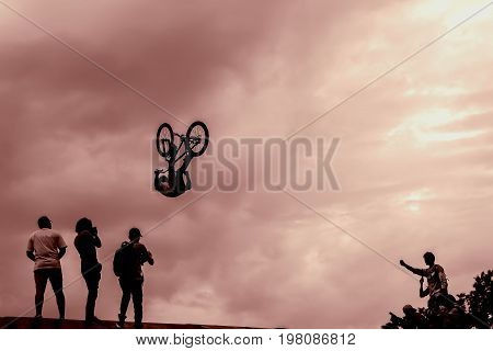 Extrem Sport and risk. Performance at competitions. Silhouette of unidentified young man performs stunts on the background of vivid sky. With place for your text, for background use