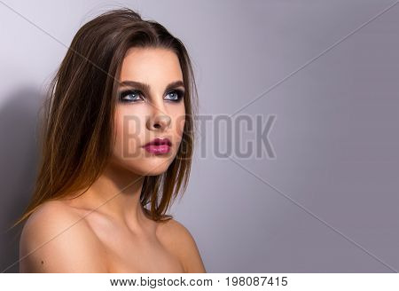 Fashionable portrait of a girl model. Fashion, smoky eyes makeup. Glamour style lady, nude shoulders.