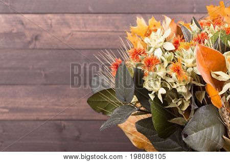 Autumn color dried flower bouquet on a wood background