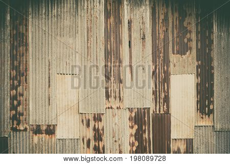 Old rusty corrugated tin zinc metal wall in vintage tone with vignetting.