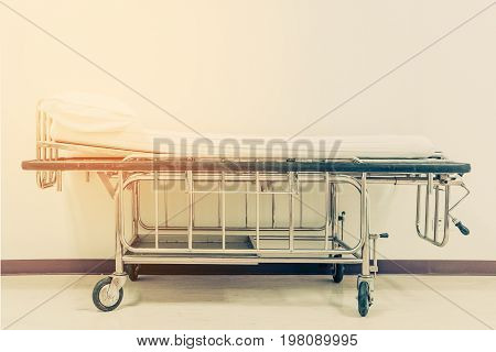 Empty Stretcher Trolley Or Hospital Trolley For Patient With White Room. Vintage Tone.