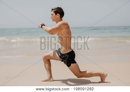 Active Athlete Runner Running On Sandy Beach. Man Long Jumping At Ocean, Sprinting With High Energy
