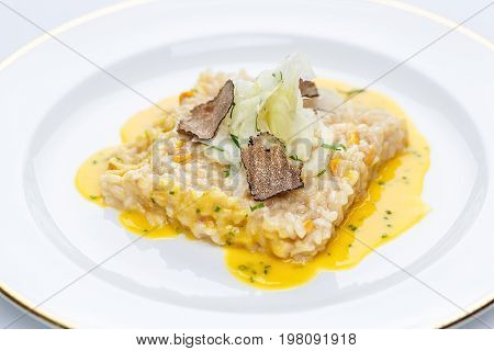 Risotto with truffles and corn sauce in white plate on white tablecloth.