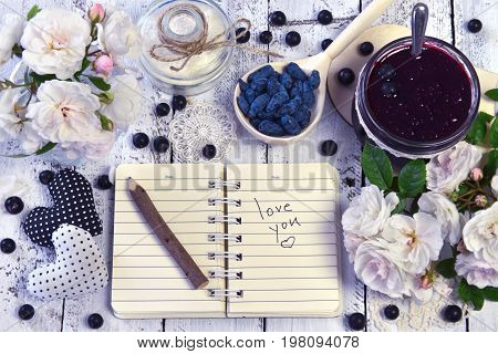 Open notebook with text love you, wild roses, jam in vintage jar and fresh berry in spoon. Making fruit jam concept. Fresh berry on wooden table, summer still life and rustic food vintage background