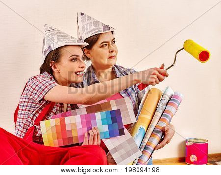 Repair home women holding color guide for wallpaper. Elderly mother and young daughter renovation apartment . They took loan for repairs.