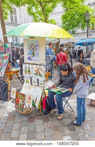 PARIS, FRANCE - JUNE 6, 2012: A young girl watches an artist painting at her outdoor stall in Montmartre in Paris.