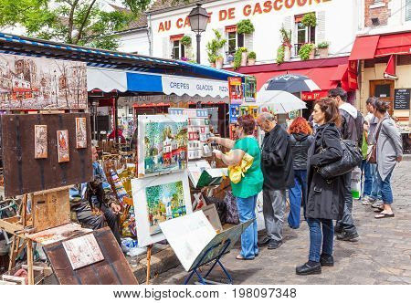 PARIS, FRANCE - JUNE 6, 2012: Tourists viewing art for sale in Montmartre in Paris.