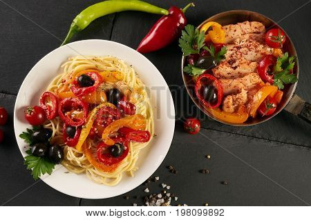 Italian pasta with a parmesan cheese basil olives paprica and tomatoes on a plate and fried chicken fillet on a pan on a dark slate table.Tasty pasta with cheese fried chicken on black background