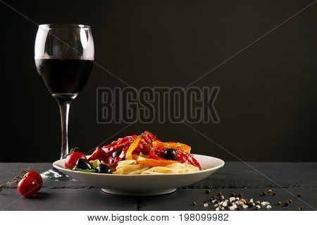 Italian pasta with a parmesan cheese basil olives paprica and tomatoes on a white plate on a dark slate isolated on black background with copy space. Tasty pasta with cheese and red dry wine glass