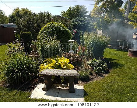 Flower garden surrounded by a stool and a smoker in the background