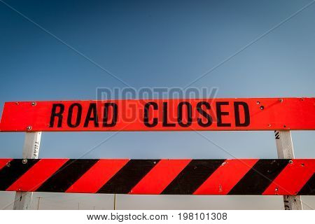 A Road Closed construction sign against a clear blue sky background.