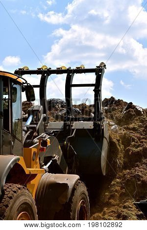 A front end loader pushes grass trimmings unto a huge compost pile.