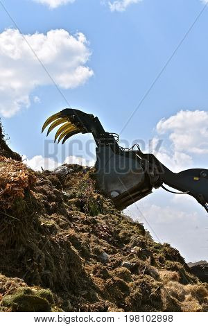 The sharp teeth of a front end loader lifts huge amounts of grass trimmings unto a compost pile,