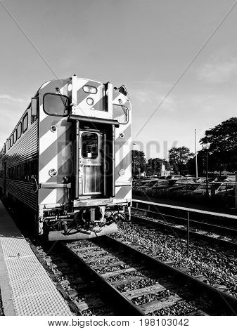 Black and White Image of commuter train arriving at station during morning rush hour