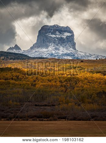 Chief Mountain in Autumn with layers of aspen trees with fall colors in Glacier National Park, Montana, USA