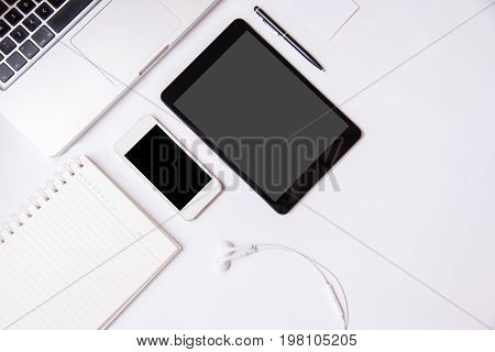 Business working at an office Modern white office desk table with laptop computer tablet smartphone with black screen notebook and earphone. Top view with copy space flat lay.