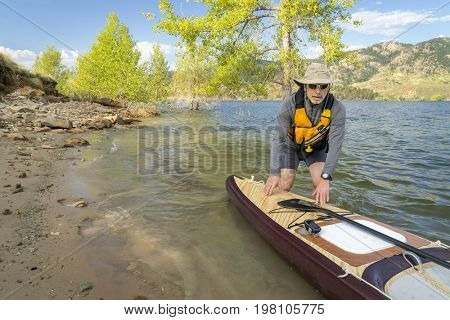Senior paddler with a large volume expedition stand up paddleboard on a shore of mountain lake - Horsetooth Reservoir in northern Colorado