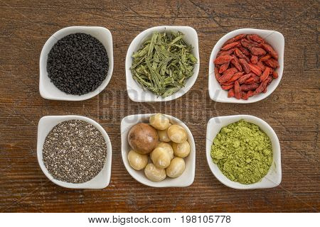 collection of superfoods in small ceramic bowls against rustic wood: black cumin seeds, macadamia nuts, hemp seed hearts, goji berry, stevia herb and chia seeds