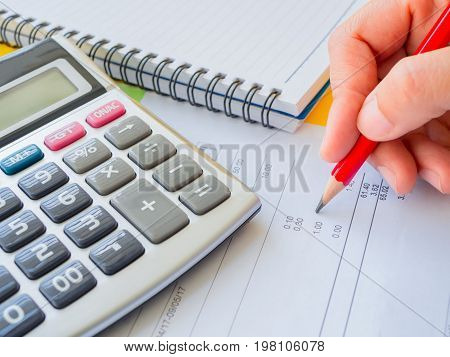 abstract money saving. Closed up woman hand using calculator with note book and red pencil in white background.
