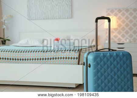 Blue suitcase in light hotel room