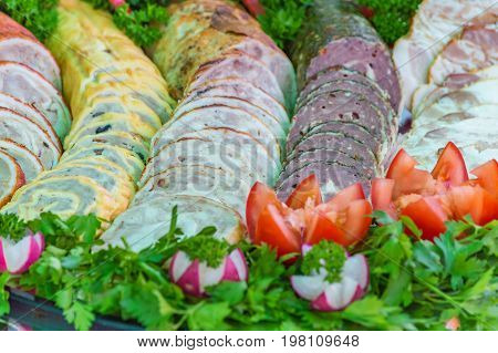 beautifully served with sliced deli meats decorated with greens and vegetables