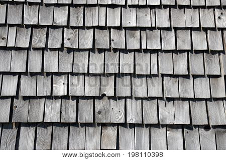Traditional wooden shingles on a roof of the house.