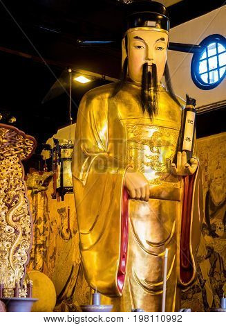 Shanghai, China - Nov 6, 2016: Inside the 600-year-old Old City God Temple. Statue of a Taoist Deity Judge with a scroll in hand that reminds visitors to