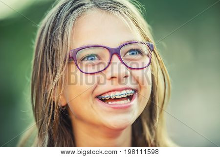 Happy Smiling Girl With Dental Braces And Glasses. Young Cute Caucasian Blond Girl Wearing Teeth Bra