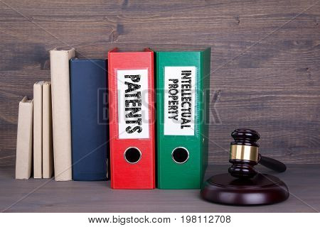 Patents and Intellectual Property. Wooden gavel and books in background. Law and justice concept.
