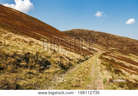 Road Through Mountains With Reddish Hills