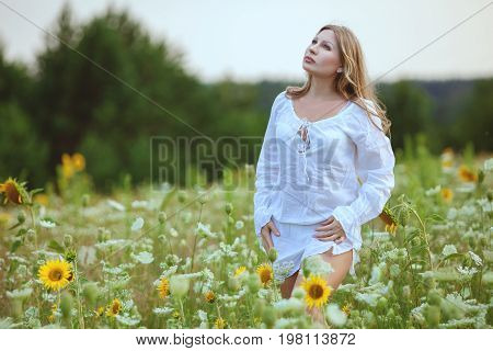 Young woman in wildflowers on a warm summer day.