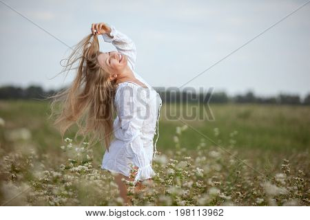 Happy woman is standing in the field and touching her long hair. She is ecstatic about nature.