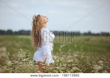 Woman in the field enjoys she enjoys the freshness of nature.