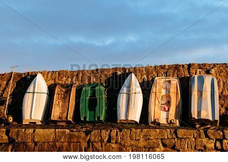 6 rowing boats standing upright facing a stone wall on a pier