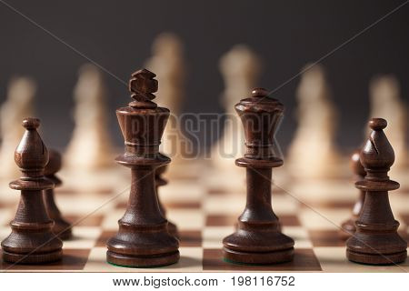 Wooden chess pieces arranged on the chess board before the game.